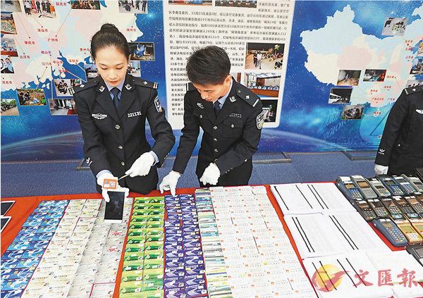 ■警方搜獲電騙案中大量銀行卡和身份證。  香港文匯報記者敖敏輝 攝